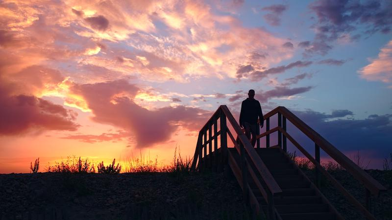 Une silhouette sur un pont accède à la plage sur fond de Soleil couchant